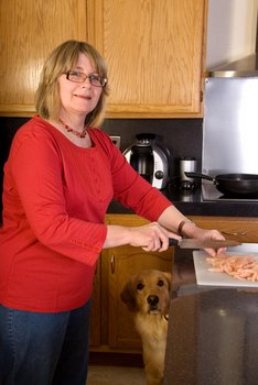 A dog with pet health insurance watches as his master prepares a meal.