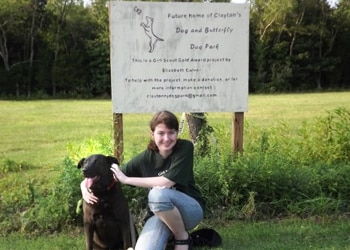Elizabeth and her dog Eagle, who has pet insurance from Pets Best, pose together at the future dog park site in Clayton, NJ.