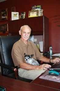 Pet insurance pioneer and founder Dr. Stephens sits with his dog.