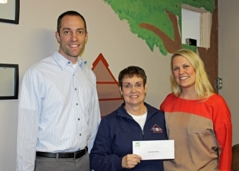 Pets Best employees and the Meridian Valley Humane Society vice president pose together with the matching donation check.