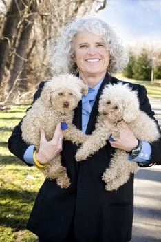 Diane Ayres of SNIP holds two small dogs.