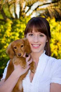 A woman holds a dog with dog insurance.