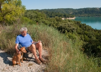 A retired senior citizen man with his dog are protected by Pets Best Insurance.