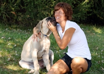 A dog licks a woman's face, making her laugh.