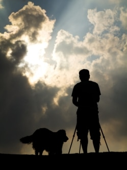 a dog insured by Pets Best Insurance and his pet parent stand on a mountain as the sun sets.