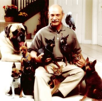 The founder of pet insurance in the US, Dr. Stephens, sits with his pets.