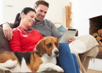 Pet parents sit on the couch with their dog, as they get an email on their Ipad from Pets Best Pet Insurance that their claim has already been processed and their money will be deposited into their checking account via direct deposit.