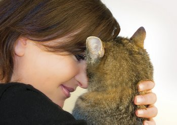 A woman snuggles with her cat.