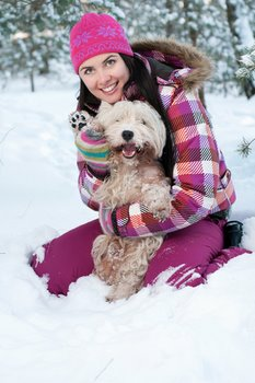 A woman and her dog play in the snow.