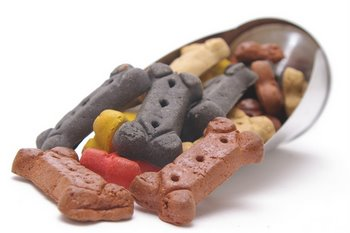 An assortment of colorful dog treats in a scoop