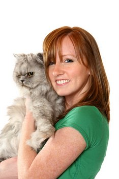 A woman holds her cat after purchasing cat insurance.
