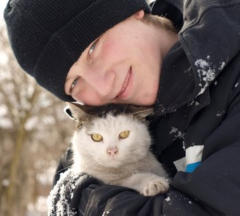 A cat with pet insurance keeps warm outside.